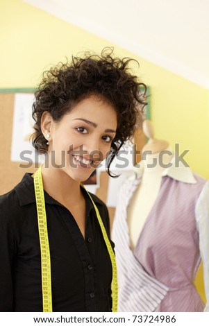 Portrait of young hispanic female dressmaker with mannequin in background. Vertical shape, waist up, copy space - stock photo
