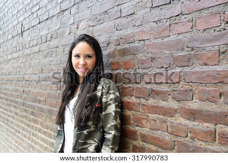 Portrait of young hispanic woman posing against a brick wall.  - stock photo
