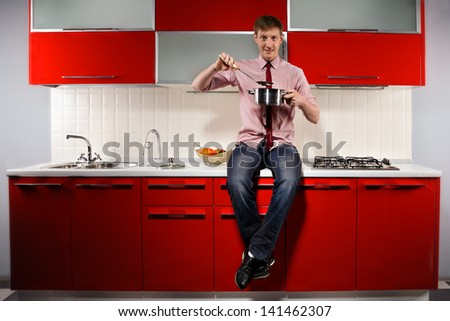 Portrait of  young hungry man filching  pan with soup on red kitchen - stock photo