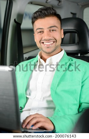 Portrait of young Indian business man sitting in the back seat of your car. - stock photo