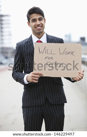 Portrait of young Indian businessman holding 'Will Work for Food' sign - stock photo