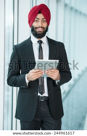 Portrait of young indian businessman with tablet in suit and turban. - stock photo