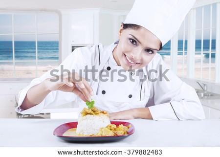 Portrait of young indian chef woman decorating delicious food in the kitchen - stock photo