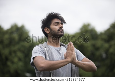 Portrait of young Indian man doing yoga exercise in park - stock photo