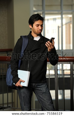 Portrait of young Indian student using cell phone indoors - stock photo