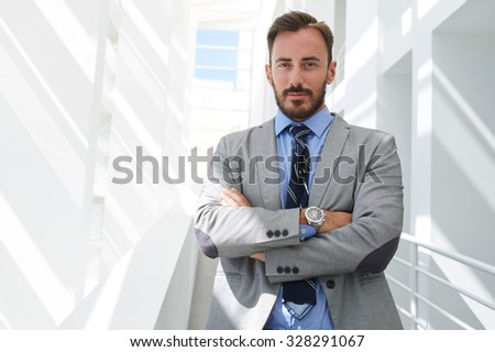 Portrait of young intelligent man lawyer standing with crossed arms in modern office building interior, successful male bank employee dressed in luxury suit posing with copy space area for your text  - stock photo