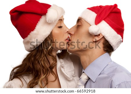 Portrait of Young kissing couple in Christmas hats. Isolated over white background - stock photo