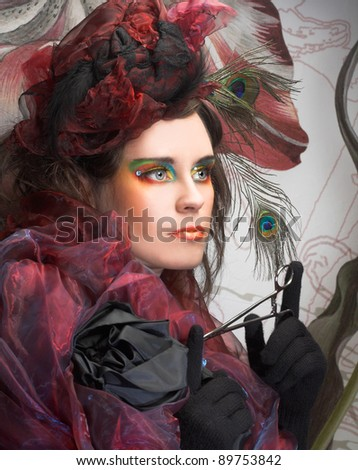 Portrait of young lady in hat with peacock feathers anf in blue beads on her hand. - stock photo