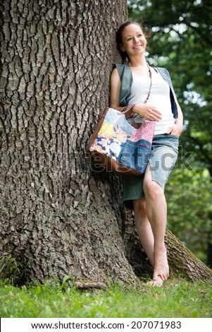 Portrait of young lady with handbag standing by the tree in a park - stock photo