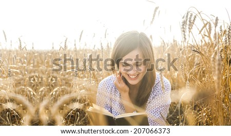 Portrait of young latin hispanic girl sitting on golden reap wheat in yellow sunset field reading black book on summer nature background Woman with long brunette hair laugh and looking at paper page - stock photo