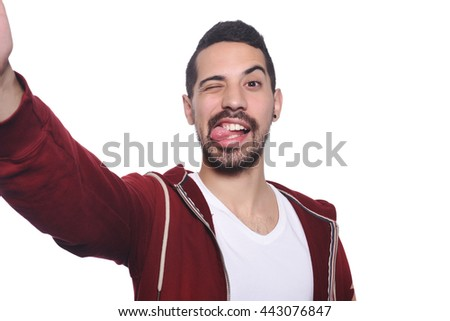 Portrait of young latin man taking selfie. Isolated white background. - stock photo