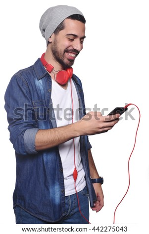 Portrait of young latin man with headphones and smartphone. Isolated white background. - stock photo