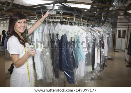 Portrait of young laundry owner with receipt checking clothes - stock photo