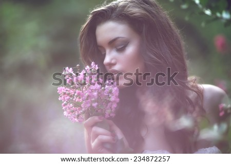 Portrait of young lovely woman in spring flowers. Beauty Romantic Girl Outdoors.  Blowing Long Hair. Glow  Backlit.  - stock photo