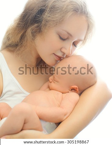 Portrait of young loving mother holding on hands sleeping infant - stock photo