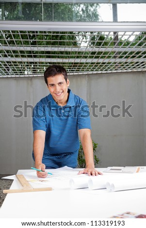 Portrait of young male architect in casual wear working on blueprints - stock photo
