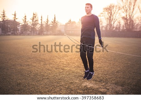 Portrait of young male athlete skipping rope. Selective focus, depth of field, movement blur   - stock photo