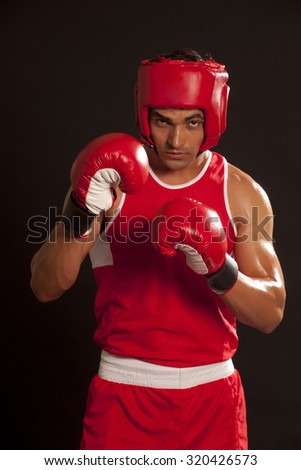 Portrait of young male boxer wearing gloves and head protector standing against black background - stock photo