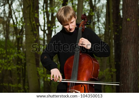 Portrait of young male cello player in green spring forest. Blond hair. Playing classic instrument. Dressed in black. Artistic looking. - stock photo