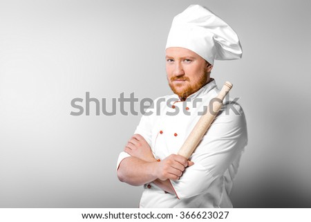 Portrait of young male chef in white uniform. Head-cook holding rolling-pin in one hand - stock photo