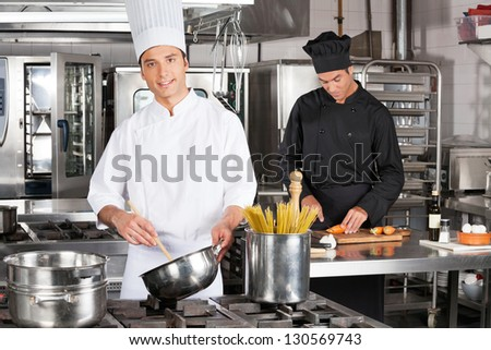 Portrait of young male chef preparing spaghetti with colleague chopping carrots in kitchen - stock photo