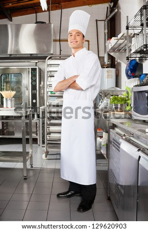 Portrait of young male chef standing with arms crossed in restaurant kitchen - stock photo