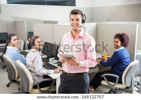 Portrait of young male customer service executive holding tablet computer while colleagues looking at him in call center - stock photo
