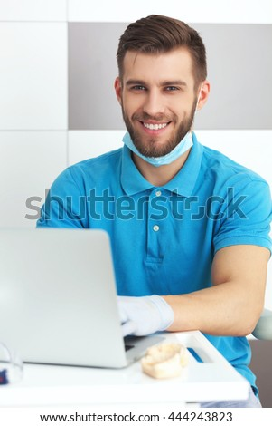 Portrait of young male dentist working with notebook. - stock photo