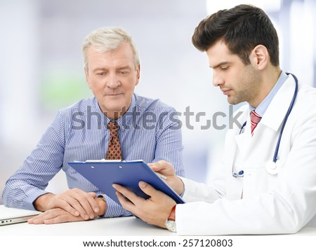 Portrait of young male doctor sitting at desk with elderly patient and consulting at hospital.  - stock photo
