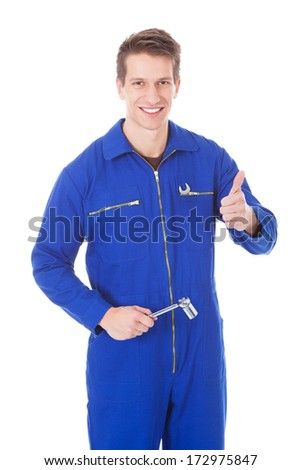 Portrait Of Young Male Mechanic Holding Equipment Over White Background - stock photo