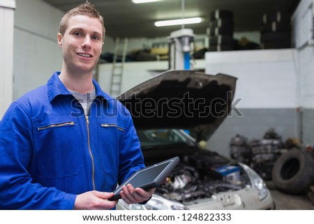 Portrait of young male mechanic with digital tablet at garage - stock photo