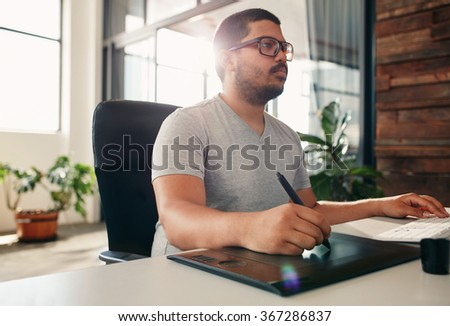 Portrait of young male photo editor at work in his office. Male graphic designer working at his desk using digital graphic tablet and digitized pen. - stock photo