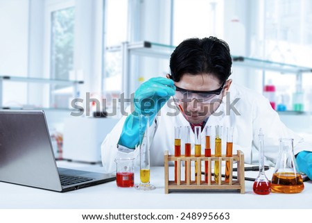 Portrait of young male scientist studying chemical liquid in the modern laboratory - stock photo