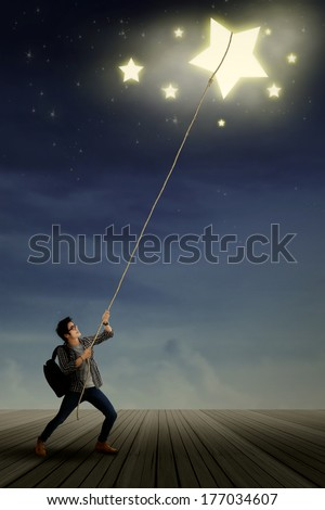 Portrait of young male student pulling down the stars with rope - stock photo