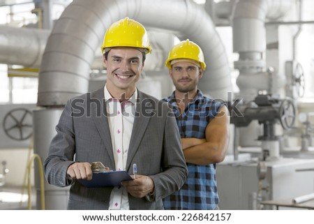 Portrait of young male supervisor holding clipboard with manual worker in background at industry - stock photo