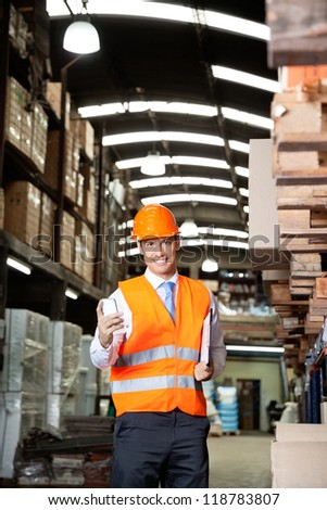 Portrait of young male supervisor in orange protective vest using cell phone at warehouse - stock photo