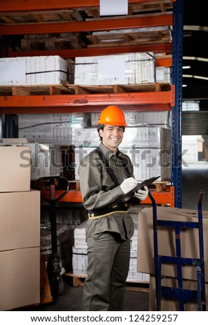 Portrait of young male supervisor writing on clipboard at warehouse - stock photo