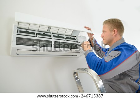 Portrait Of Young Male Technician Repairing Air Conditioner - stock photo