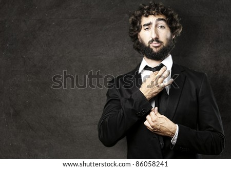 portrait of young man adjusting his suit against a grunge background - stock photo