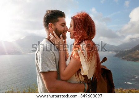 Portrait of young man and woman about to share a romantic kiss. Affectionate young couple enjoying their love in nature outdoors on a sunny day. - stock photo