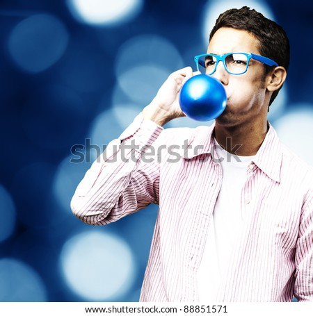 portrait of young man blowing a balloon against a abstract background - stock photo
