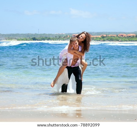 Portrait of young man carrying his cute young girlfriend on his back. The happy couple comes out of the ocean - stock photo