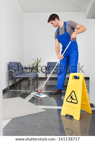 Portrait Of Young Man Cleaning The Floor With Mop In Office - stock photo