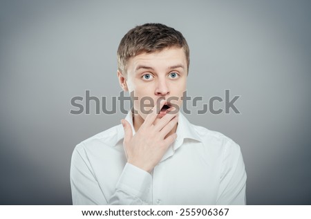 portrait of young man covering his mouth with hand  - stock photo