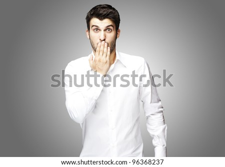portrait of young man covering his mouth with hand over grey - stock photo
