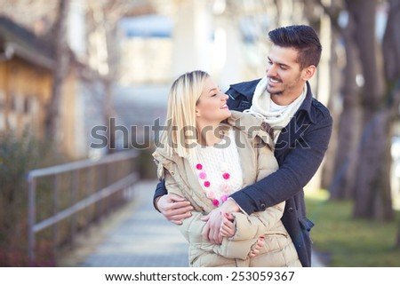 Portrait of young man embracing his girlfriend during their romantic walk in the city. - stock photo
