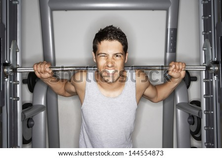 Portrait of young man grimacing while lifting weights at gym - stock photo