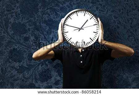 portrait of young man holding a clock against a vintage background - stock photo