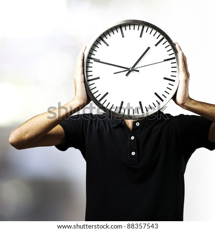 portrait of young man holding a clock with his hands against a abstract background - stock photo