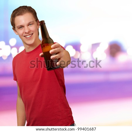 portrait of young man holding beer against a abstract background - stock photo